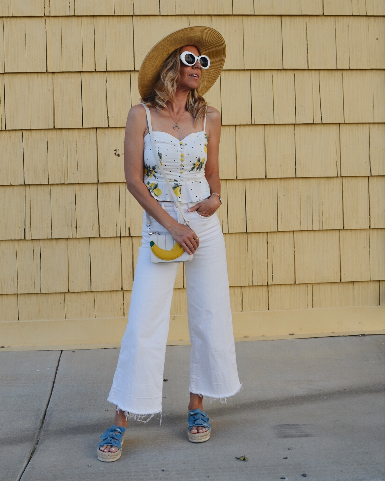 THE MUST HAVE SHOE TREND- PLATFORMS- Jaclyn De Leon Style + espadrille slip on denim sandals + white culottes + lemon top + fruit inspired tank + straw hat + retro style sunglasses + bananna handbag + casual street style + what to wear this summer