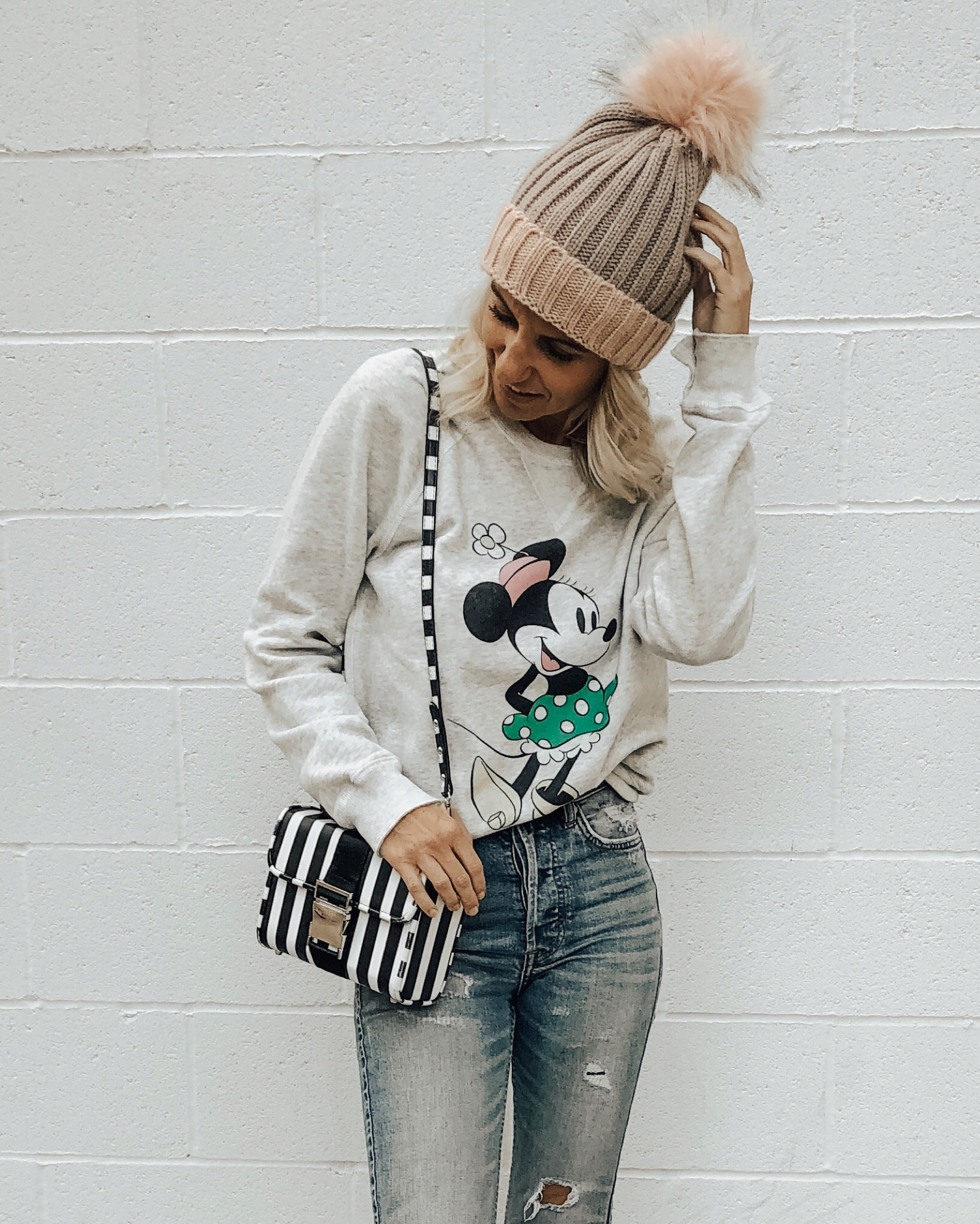 DECEMBER TOP 10- Jaclyn De Leon Style + Minnie Mouse sweatshirt + Disney inspired outfit + casual and cozy top + winter style + mom style + disney addict + pom pom beanie + striped handbag + distressed denim